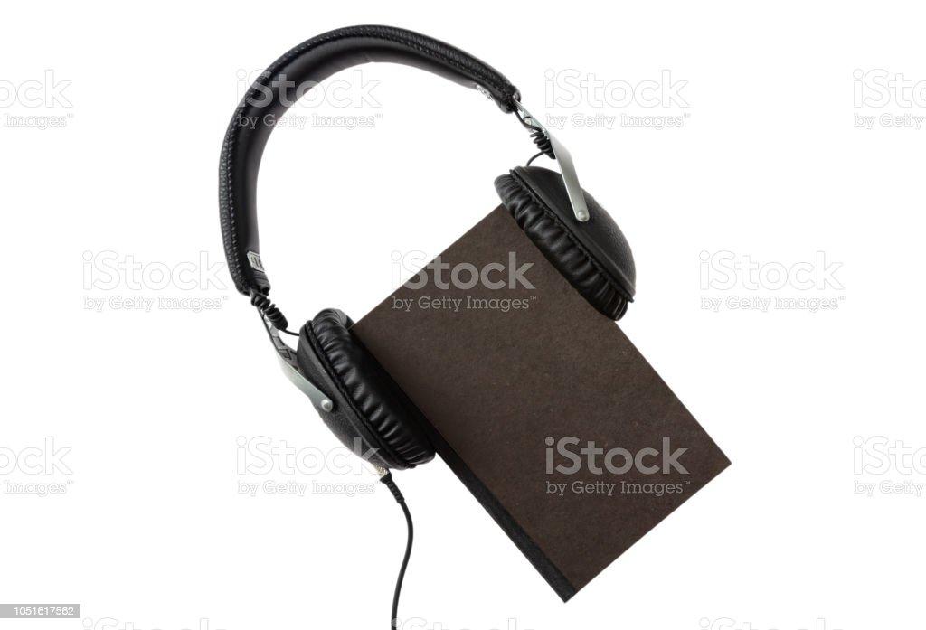 Audio-livro. Livro negro e fones de ouvido conjunto isolado no fundo branco, vista superior - foto de acervo