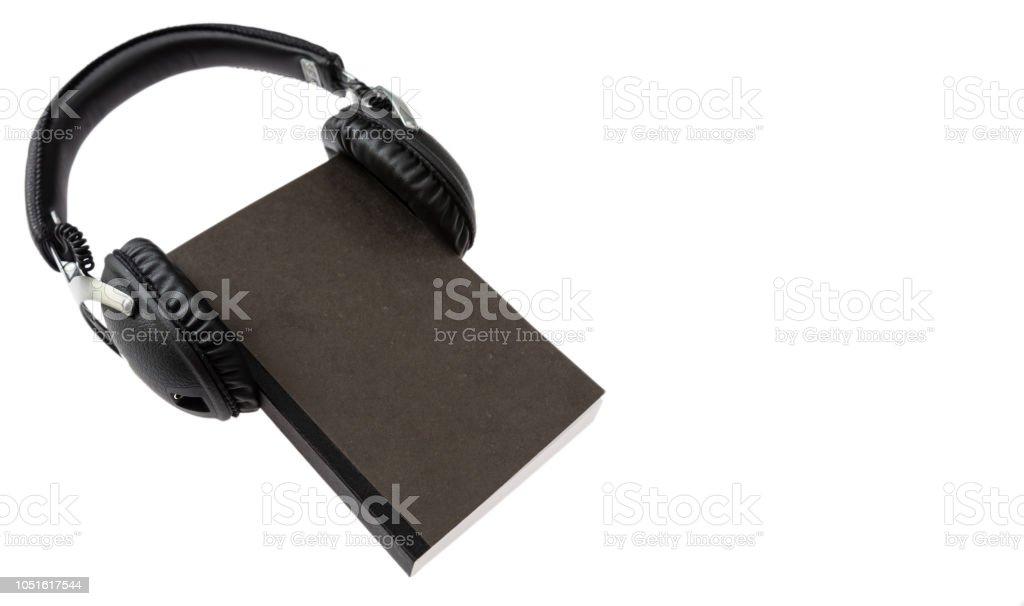 Audio-livro. Livro negro e fones de ouvido sem fio conjunto isolado no fundo branco - foto de acervo