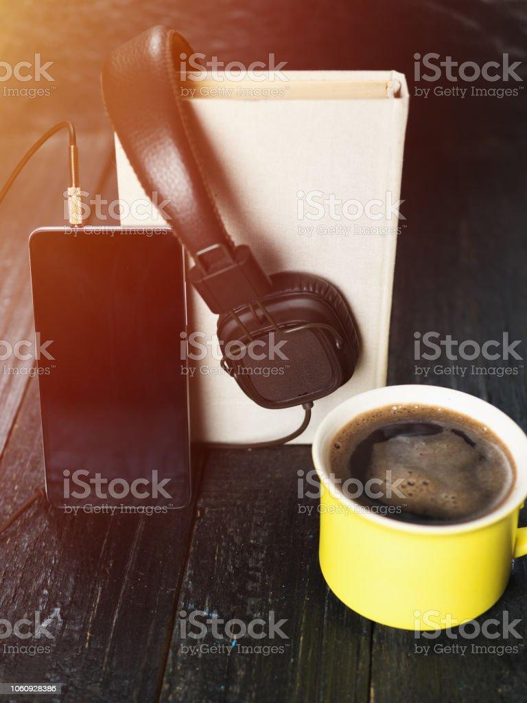 Conceito de áudio livro. Fones de ouvido, o café e o livro sobre a mesa de madeira - foto de acervo
