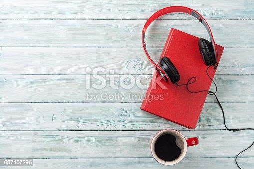 istock Audio book concept. Headphones, coffee and book 687407296