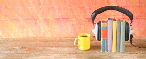 Hörbuch-Konzept, mit Buch, Kopfhörer und Tasse Kaffee, Panoramaformat auf gruseliger Herkunft, guter Kopierplatz – Foto