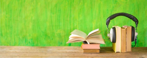 Hörbuchkonzept mit offenem Buch und Kopfhörern, Panoramaformat auf grungem Hintergrund, guter Kopierraum – Foto