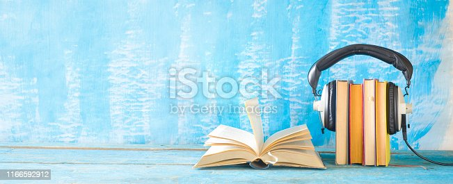 istock audio book concept with open book, row of books an headphones, panorama format on grungy background, good copy space 1166592912