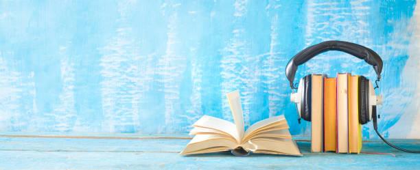 Hörbuchkonzept mit offenem Buch, Bücherreihe und Kopfhörer, Panoramaformat auf grungem Hintergrund, guter Kopierraum – Foto