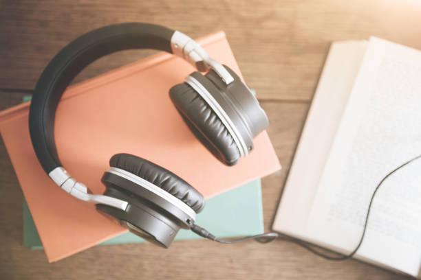 concepto de libros de audio con el fondo de la mesa de madera rústica - auriculares equipo de música fotografías e imágenes de stock