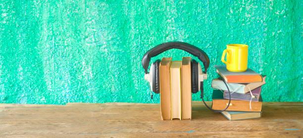 Hörbuch-Konzept, mit Stapeln von Büchern, Kopfhörer und Tasse Kaffee, Panorama, gute Textfreiraum – Foto