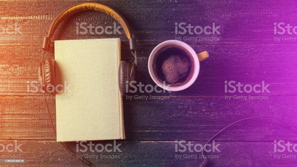 Audio-livro em fundo escuro de madeira, com espaço de cópia - foto de acervo