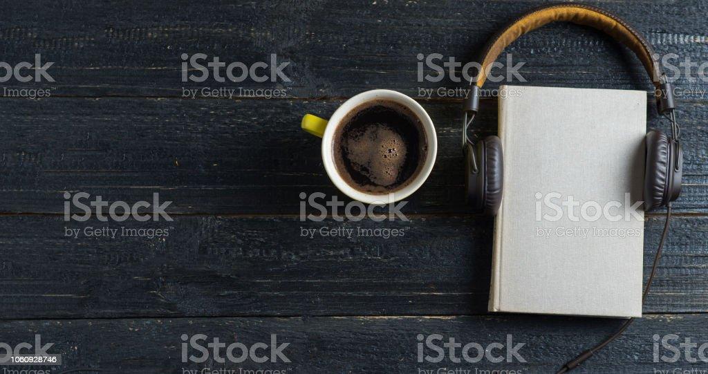 Livro de áudio com fones de ouvido e caneca de café no fundo escuro de madeira. O conceito da biblioteca eletrônica - foto de acervo