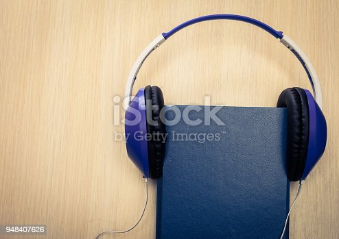 istock Audio books concept with old book and headphones 948407626