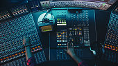 istock Audio Engineer, Musician, Artist Works in the Music Record Studio, Control Desk Mixer with Equalizer. Hand Moving Fader, Buttons to Broadcast, Record, Play Song. Neon Colors. Top Down View 1250963278