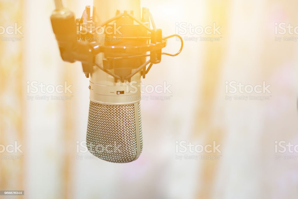 audio Microphone in a record studio or concert hall ,above recording studios mixer sound mixing mic console board,selective focus,vintage color stock photo