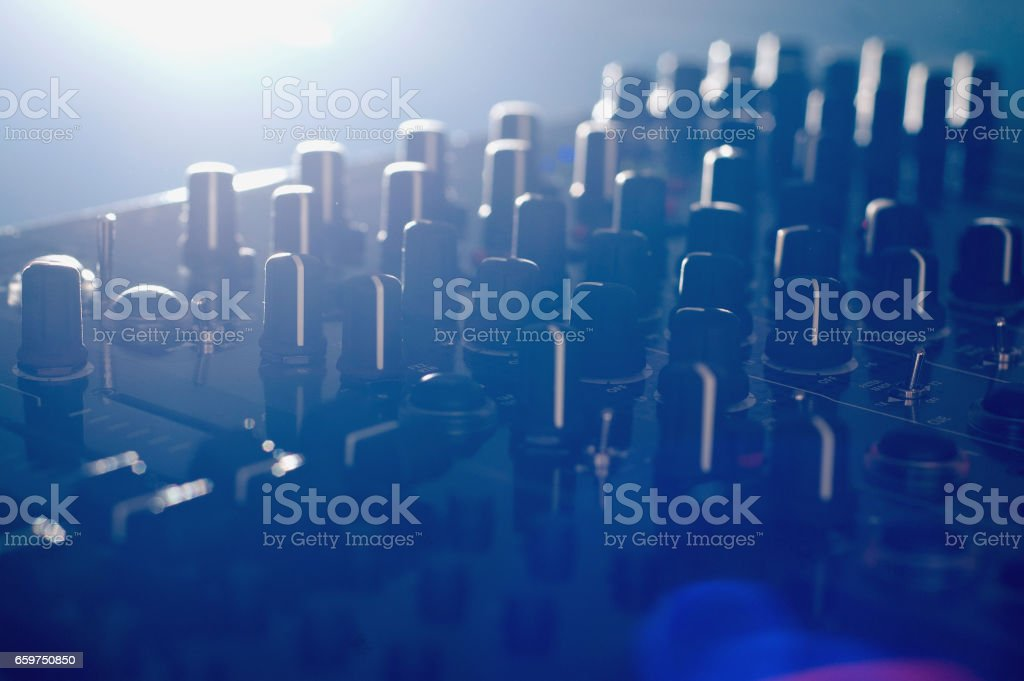 DJ audio mixer with side light and lens flare close up stock photo