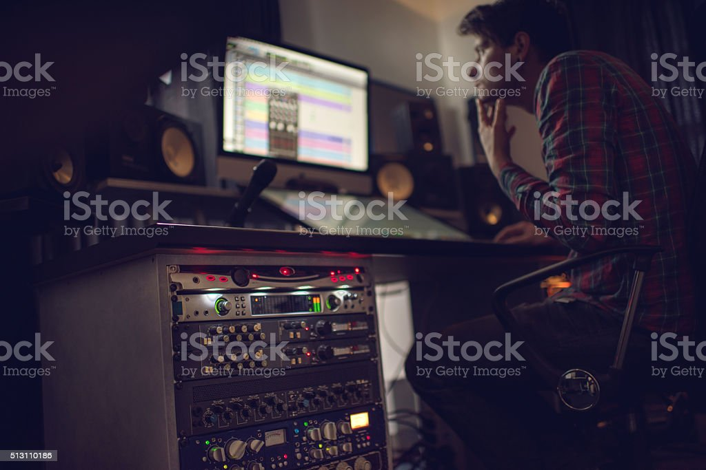 Audio rack in recording studio with producer in the background. stock photo