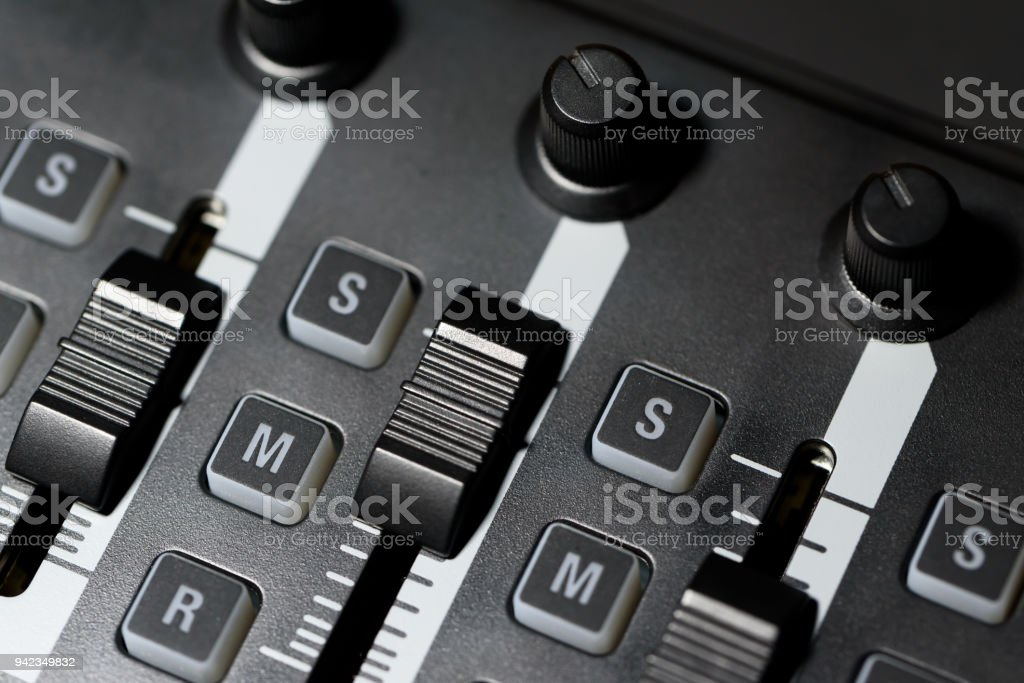 Macro close up of audio studio mixer volume level sliders and dials...