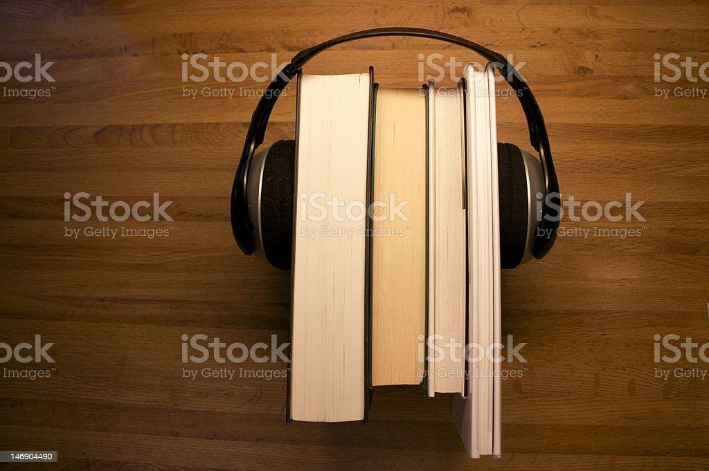 Audiobook composition with books between headphones stock photo