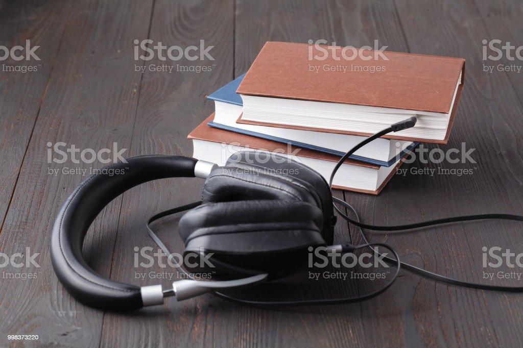 Conceito de audiobook com fone de ouvido e papel livro na mesa - foto de acervo