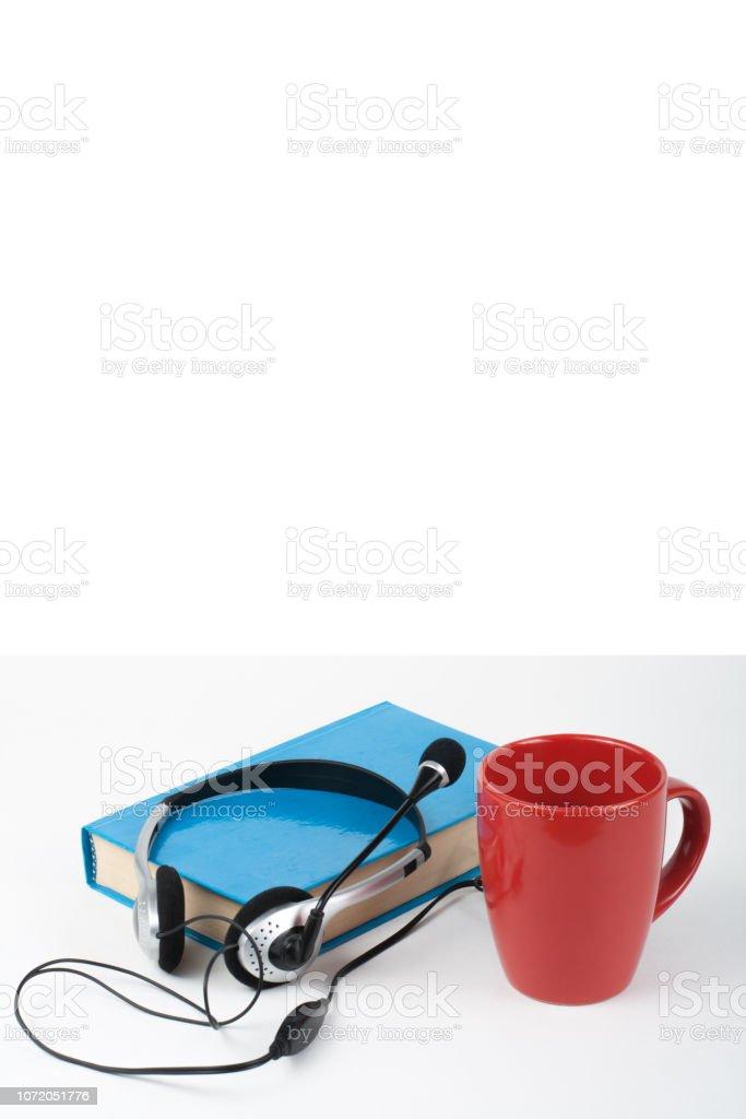 Audiobook em fundo branco. Fones de ouvido tapou-azul livro de capa dura, capa vazia, copo vermelho, espaço de cópia para o texto do anúncio. Conceito de EAD, educação a distância. - foto de acervo