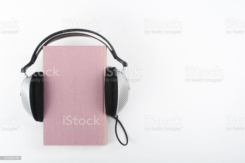 Audiobook em fundo branco. Fones de ouvido tapou rosa livro de capa dura, capa vazia, copie o espaço para o texto do anúncio. Conceito de EAD, educação a distância. - foto de acervo