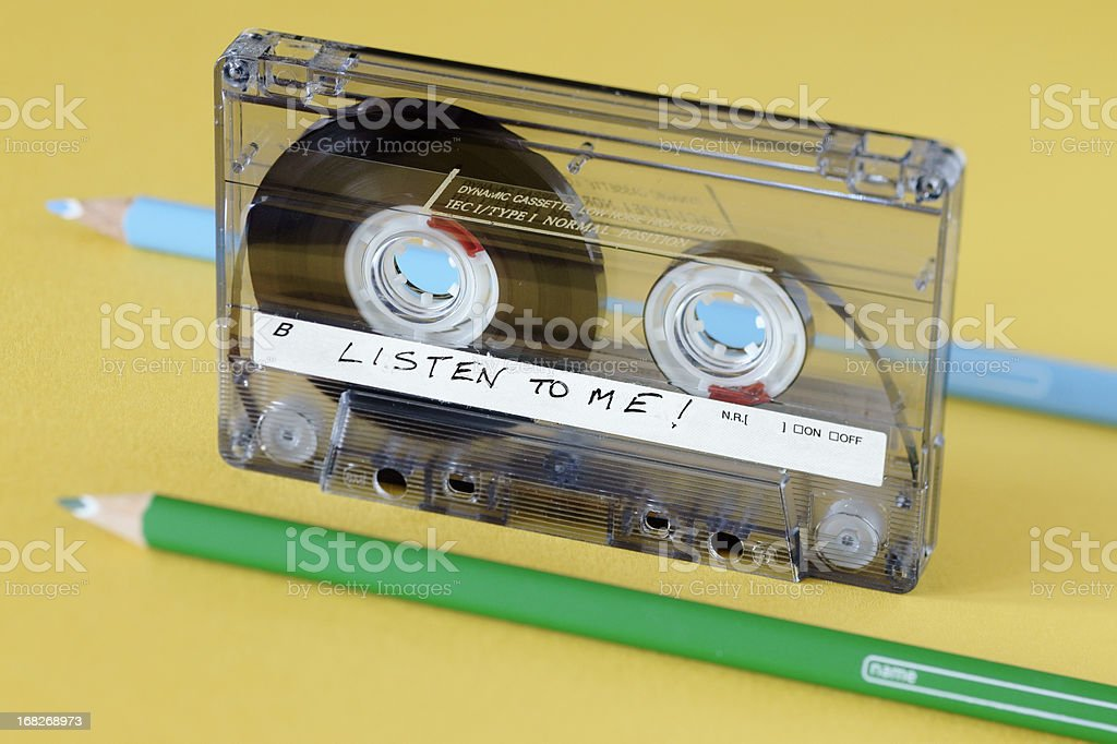Audiocassette and two pencils normally used to wind and rewind One audiocassette and two parallel coloured pencils. Tilted plane of focus. Audio Cassette Stock Photo