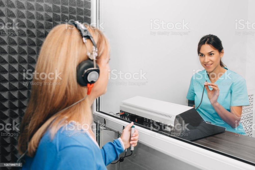 audiologist doing hearing test in special audio room stock photo