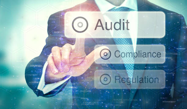 Audit concept on a computer display. A businessman selecting a button on a futuristic display with a Audit concept written on it. obedience stock pictures, royalty-free photos & images