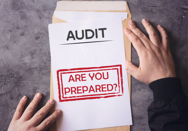 Audit Envelope Are You Prepared on white paper an yellow envelope holding by human hands stock photo