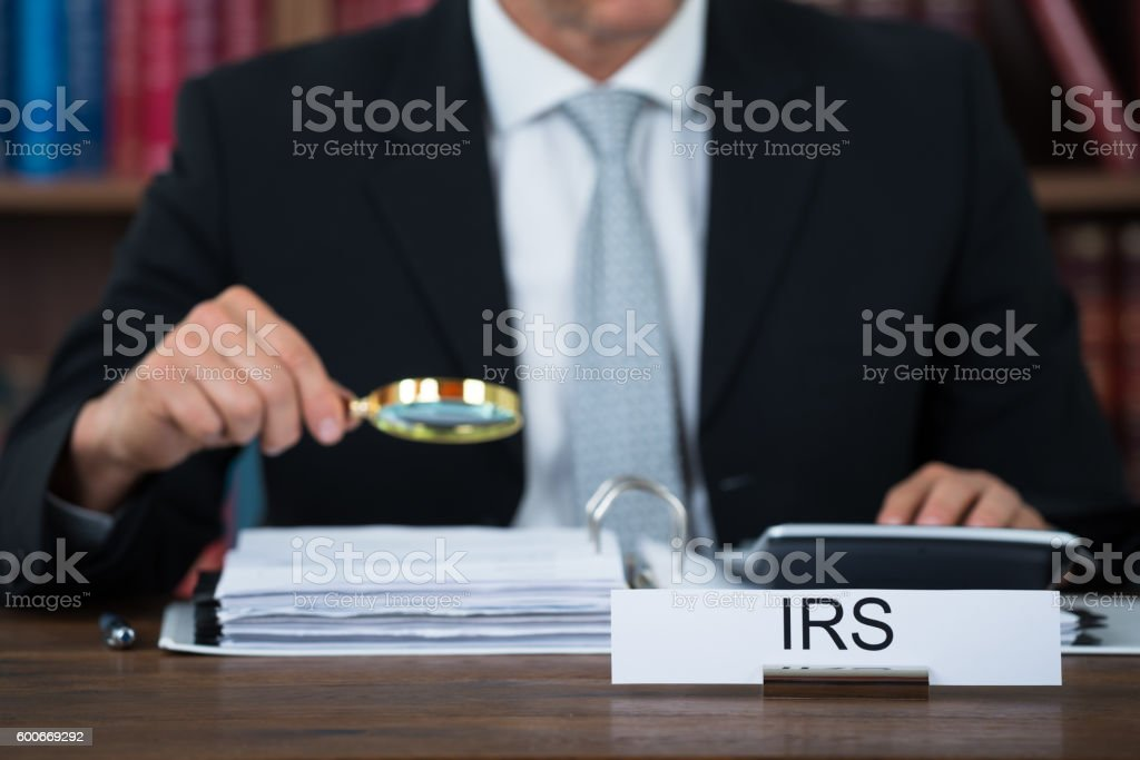 Auditor Examining Documents With Magnifying Glass At Table stock photo