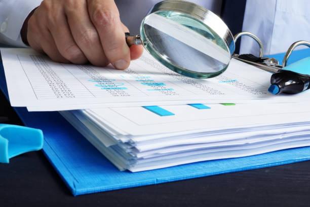 auditor is working with financial documents. audit or assessments. - wnętrze zdjęcia i obrazy z banku zdjęć