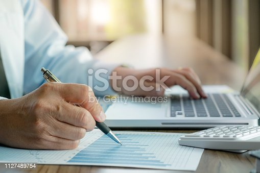istock auditor or financial inspector working on business sales report. 1127489754