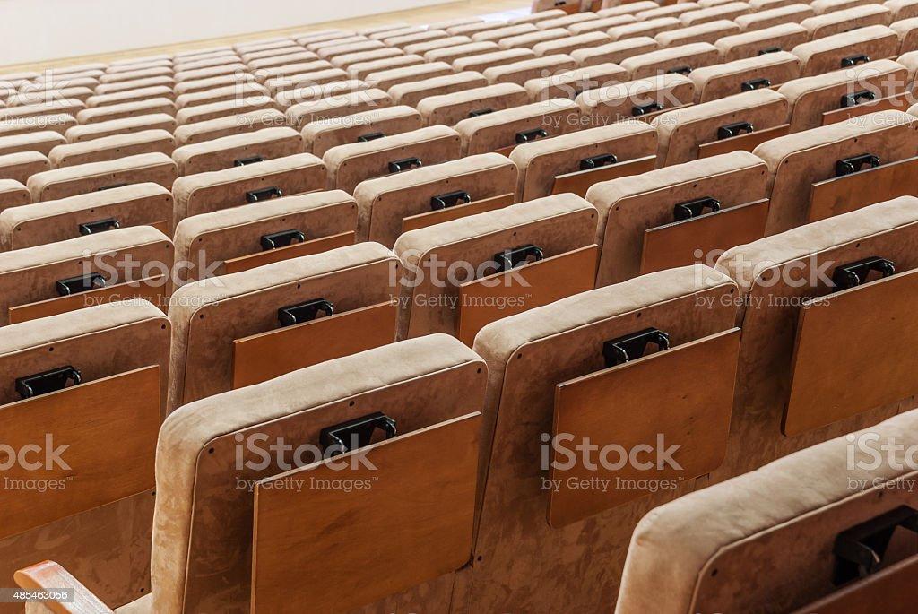 Rows of beige velvet armchairs in the auditorium