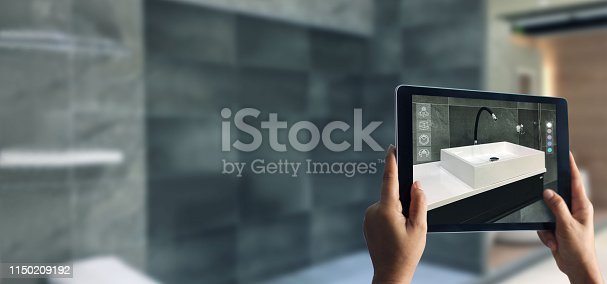 istock Augmented Reality bathroom planning. Sanitary ware. Hand holding digital tablet in real home background, AR application. A new way to experience products. 1150209192
