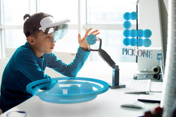 Augmented Reality - Boy playing with Robotic Hologram arm stock photo