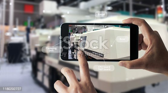 istock Augmented reality concept. AR. Industrial 4.0 , Hand of engineer holding mobile smart phone using virtual AR to check the work of electric machine on smart factory background. 1150202727