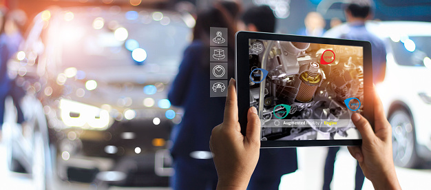 istock Augmented reality concept. AR. Industrial 4.0 , Hand of engineer holding tablet using virtual AR service application to check the work of electric machine on car showroom background 1150397385
