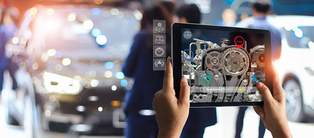 istock Augmented reality concept. AR. Industrial 4.0 , Hand of engineer holding tablet using virtual AR service application to check the work of electric machine on car showroom background 1150397386