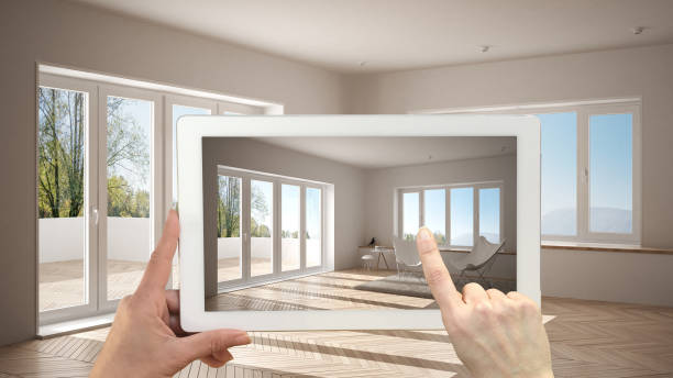 Augmented reality concept. Hand holding tablet with AR application used to simulate furniture and design products in empty interior with parquet floor, modern white living room stock photo