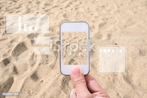 istock Augmented reality future technology concept. Hand holding smart phone use AR application to analyzed soil. 665507154