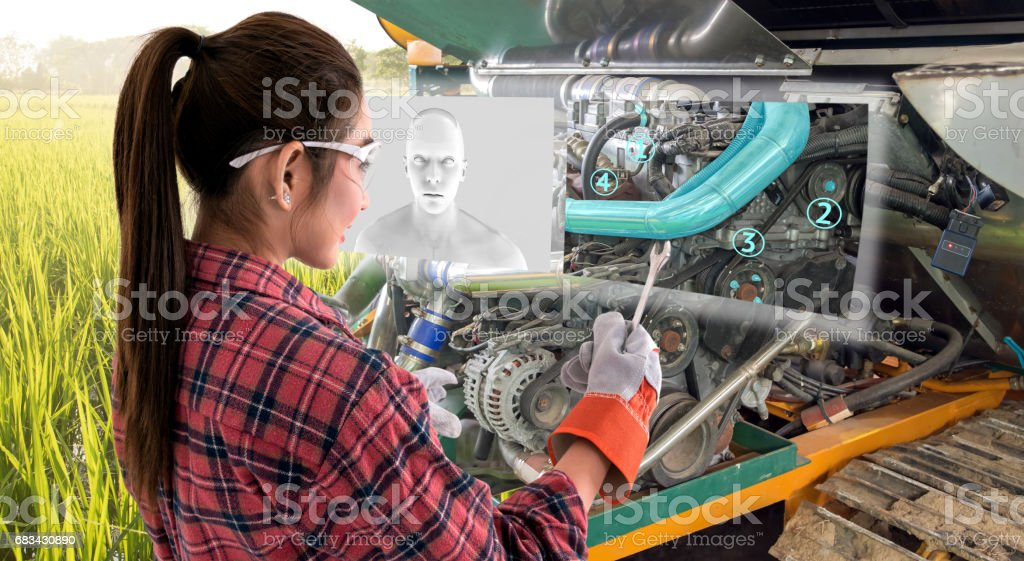 Augmented reality glasses technology , smart agriculture farm , artificial intelligence adviser, industry 4.0 concept.Young female farmer use Ar glasses to fix tractor car machine with digital screen. stock photo