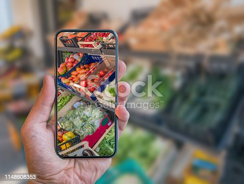 890476604 istock photo Augmented reality grocery shopping mobile app. Hand is holding cellphone with AR application scanning vegetables at food market. 1148608353