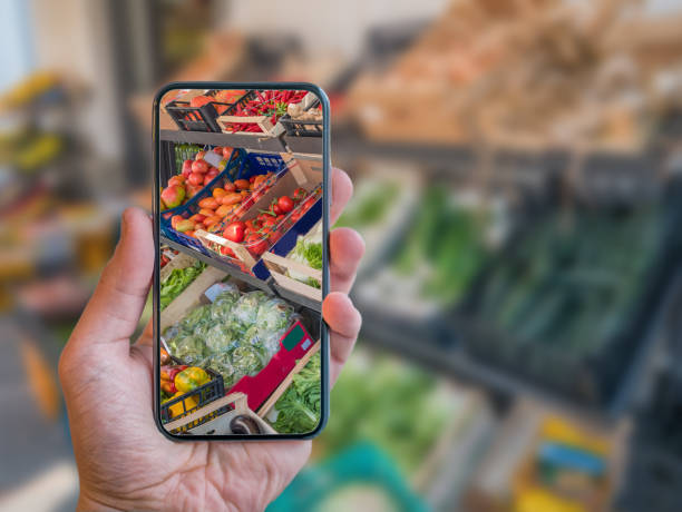Augmented reality grocery shopping mobile app. Hand is holding cellphone with AR application scanning vegetables at food market. stock photo