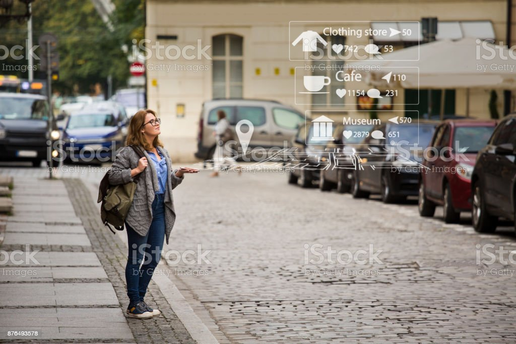 Augmented reality in marketing. Woman traveler with phone. stock photo