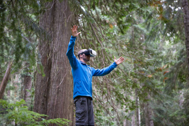 Augmented reality in the forest A young male plays with his virtual reality headgear in the forest, Whistler Canada augmented reality sustainable stock pictures, royalty-free photos & images