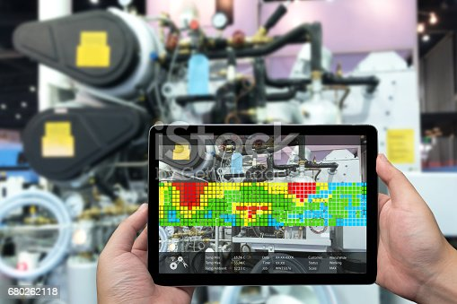 istock Augmented reality marketing and industry 4.0 concept. Hand holding tablet with AR screen application for measurement temperature machine in smart factory 680262118