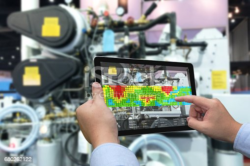 istock Augmented reality marketing and industry 4.0 concept. Hand holding tablet with AR screen application for measurement temperature machine in smart factory 680262122