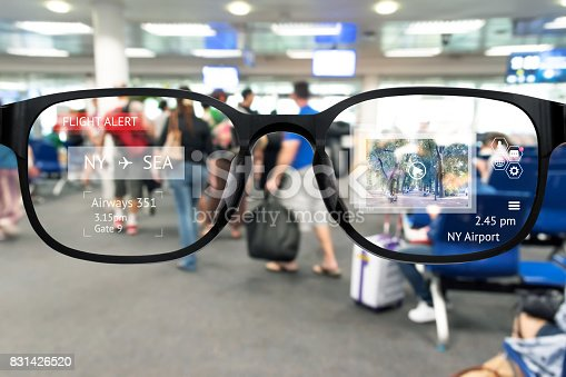 istock Augmented reality marketing and smart AR glasses technology concept. Customer using AR application to monitoring , check , alert  airline flight. Blur Airport background 831426520