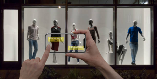 Augmented reality marketing concept. Hand holding digital tablet smart phone use AR application to check special sale price in retail fashion shop, mall interior design stock photo