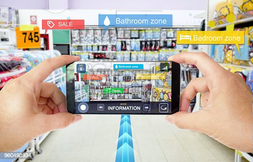 890476604 istock photo Augmented reality marketing in Department store. Hand holding smart phone use AR application to navigator, check information and promotion. 960493934