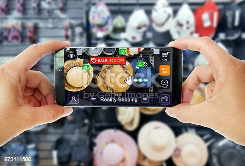 890476604 istock photo Augmented reality marketing in Department store. Hand holding smart phone use AR application to shopping online, check information and promotion. 973411560