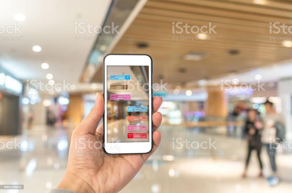 Augmented reality marketing in the shopping mall. Hand holding smart phone use AR application to check information stock photo