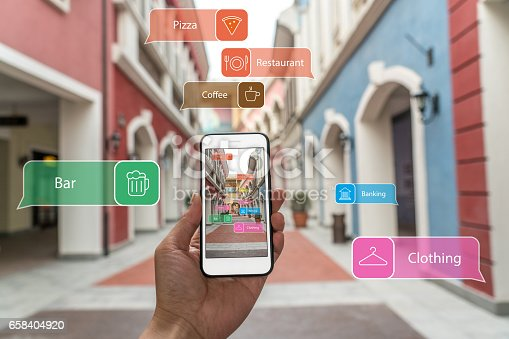 istock Augmented reality marketing street. Hand holding smart phone use AR application to check information 658404920